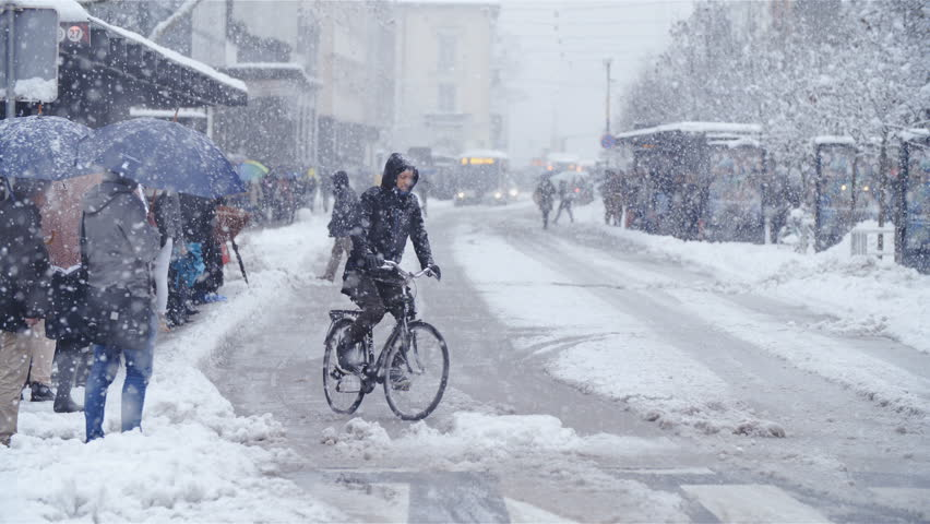 LJUBLJANA, SLOVENIA - JANUARY 2018: Person bicycling in city snow blizzard slow motion 4K. Wide view of Ljubljana city center road with a single bicyclist in focus driving over the dangerous road. | Shutterstock HD Video #1007141656
