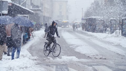 LJUBLJANA, SLOVENIA - JANUARY 2018: Person bicycling in city snow blizzard slow motion 4K. Wide view of Ljubljana city center road with a single bicyclist in focus driving over the dangerous road.