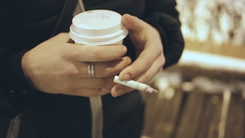 The woman is holding a Cup of coffee and a cigarette. Closeup, outdoors, real time, night, cold.