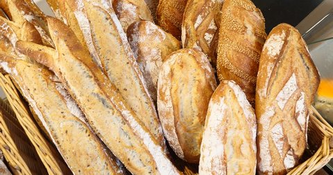 Breads and baked goods large assortment in bakery shelves with fresh baked crispy bread organic whole grain bio wheat foods boulangerie baguettes