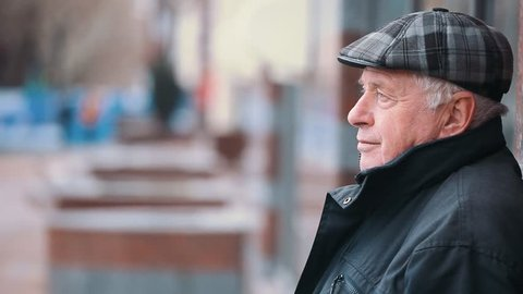 A profile of a senior man dressed in a flat cap, black zipup jacket. He stands on a park alley, waits, and thinks about his life in autumn.