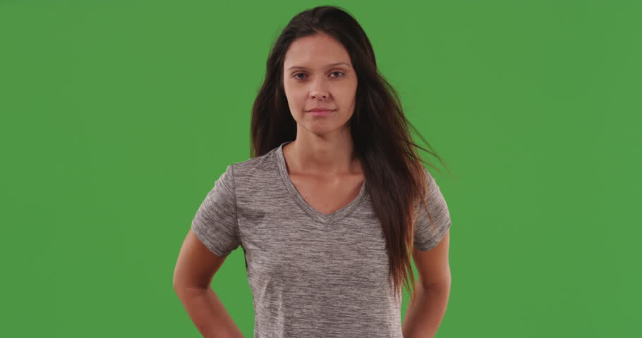 Healthy attractive young woman posed with long black hair blowing on green screen. Lovely caucasian woman standing with arms on waist in front of greenscreen wall. 4k