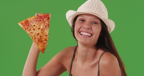 Lovely young caucasian woman posing in front of green screen wall holding slice of pizza. Happy young woman holding cheesy pizza slice and smiling on greenscreen. 4k