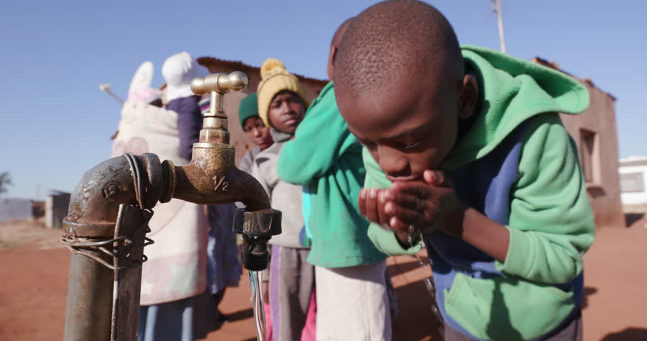 Water crisis. Young african boys drinking water from a tap while woman line up to collect water in plastic containers due to severe drought in South Africa