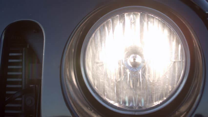 Closeup of the turning off headlight of a car.