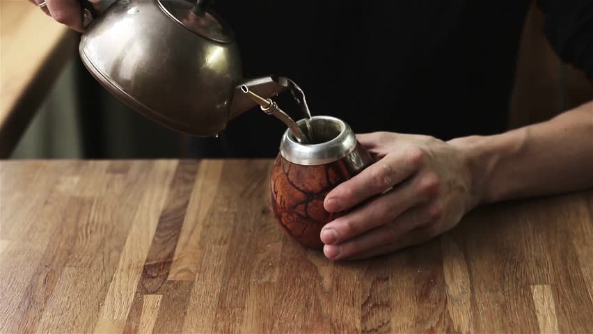 Close up of male hands preparing mate ethnic energetic drink Argentina Paraguay . man pouring water calabash gourd mate from metal kettle wooden table indoors process preparation shop advertisement.