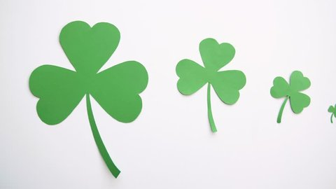 holidays and st patricks day concept - green paper shamrock on white background