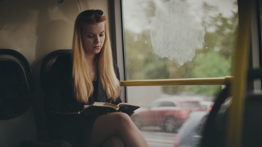 Young woman reading book and looking out window while driving in city bus | Shutterstock HD Video #1007251906