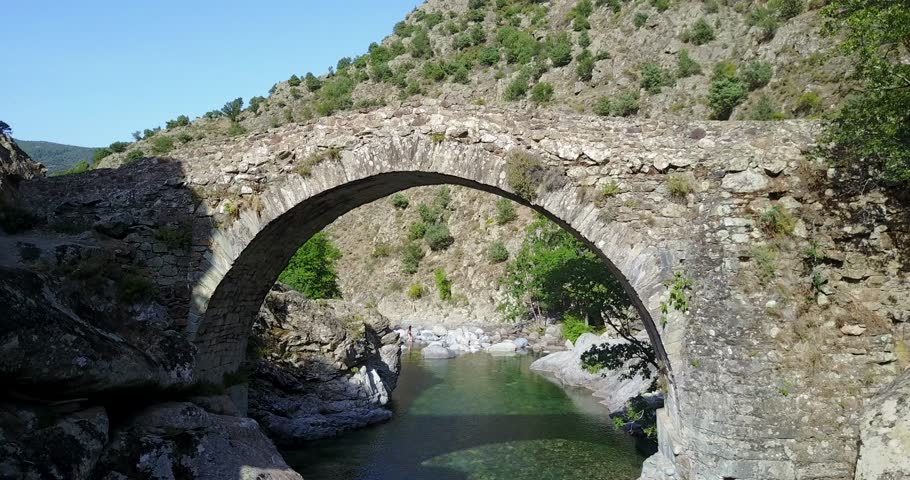 AERIAL: Flying under ancient arched Genoese stone bridge at Asco. Corsica, France.