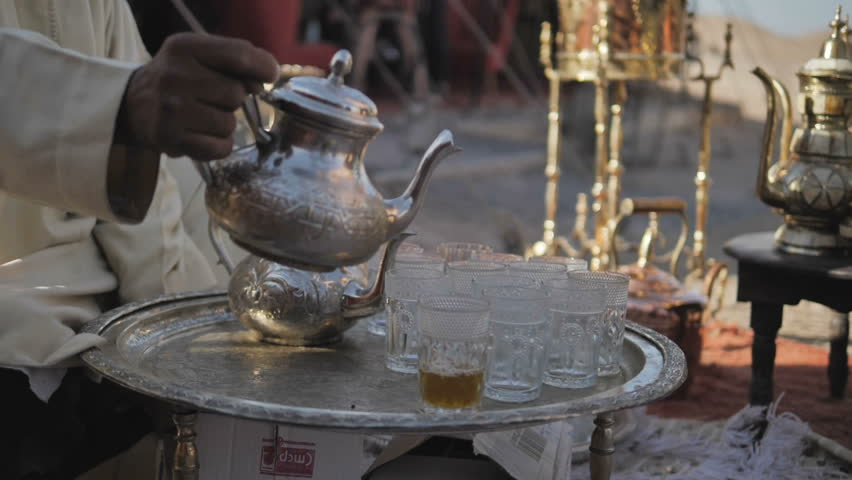 Morocco, Man pouring tea from ornate silver teapot into glasses on small table
