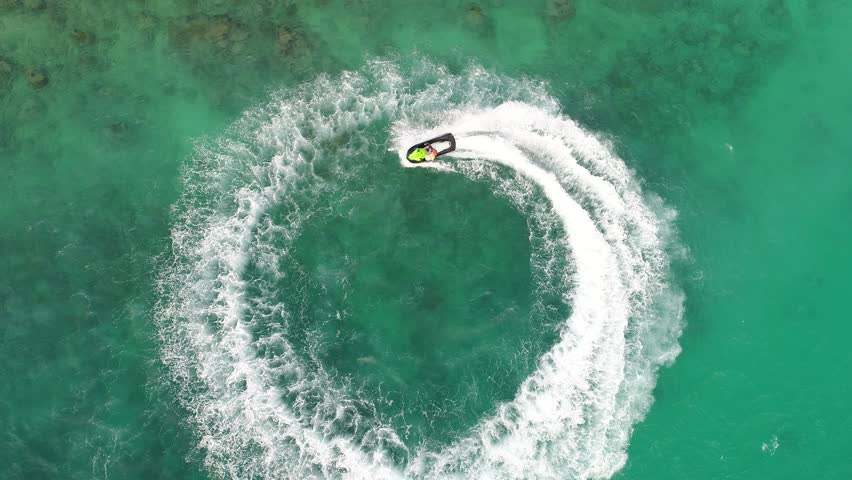 People are playing a jet ski in the sea.Aerial view. Top view.amazing nature background.The color of the water and beautifully bright. Fresh freedom. Adventure day.clear turquoise at tropical beach. | Shutterstock HD Video #1007305276