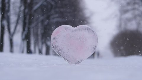 Heart made from ice stay on ground at park alley, snow fall around, slow motion shot. Blurred background, low camera position. Cold winter season, cool Saint Valentine day concept