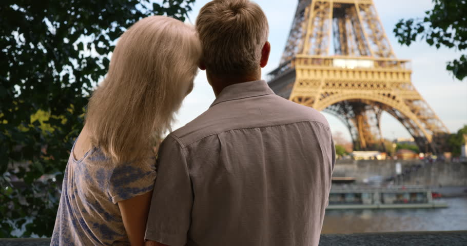 Rear view of sweet mature couple gazing at the Eiffel Tower. Romantic husband and wife sit together by the Seine. 4k | Shutterstock HD Video #1007325346