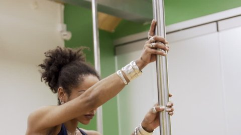 Young woman is training near pole in sports club indoors. Female dancer is engaged in poledance using metal stick in modern studio. Sexy lady with bare belly moves around shiny device, holding with