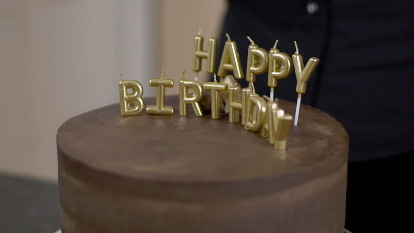 Confectioner Shows Gold Letters On A Chocolate Cake For The Holiday In Sweet Festive Dessert Candles Of Happy Birthday Are Inserted Guests And