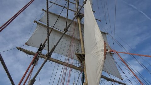 Square white sails on main mast of a sailing polish tall ship rolling with blue sky in the background