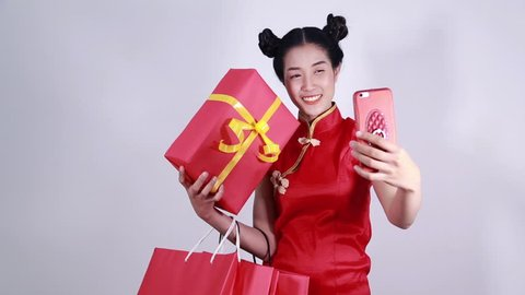 woman wear cheongsam and using mobile phone making selfie with shopping bag and gift box