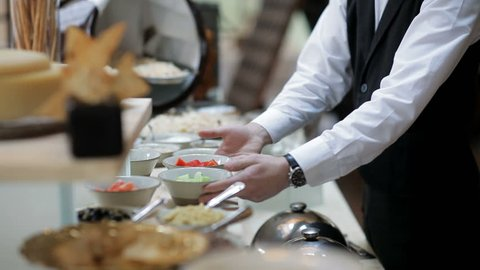 The buffet in the restaurant. The waiter serves the table