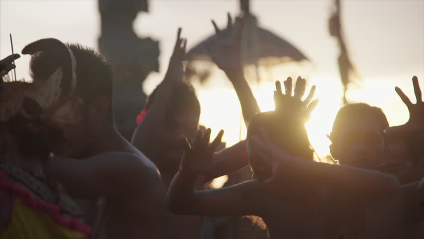 18 april 2016 Uluwatu, Bali, Indonesia. Balinese tradition performance kecak. People in silhouette wolking around in sunset light close-up heads and moving hands   Shutterstock HD Video #1007400676