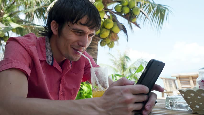 Young handsome man uses smart phone while having drinks cocktail in a tropical location with palm trees in the back. 3840x2160 | Shutterstock HD Video #1007410936
