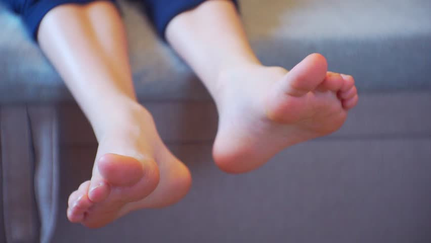 children's legs without socks carefree lying on the couch