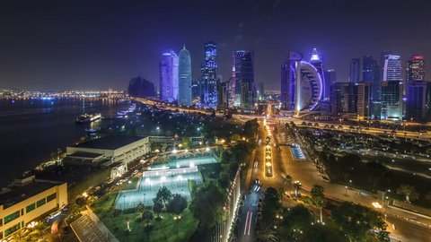 The skyline of the West Bay area from top in Doha timelapse, Qatar. Illuminated modern skyscrapers aerial view from rooftop at night. Parks and traffic on the road