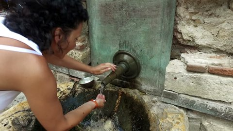 Woman drinks water from An Old Tap in Nessebar, Bulgaria