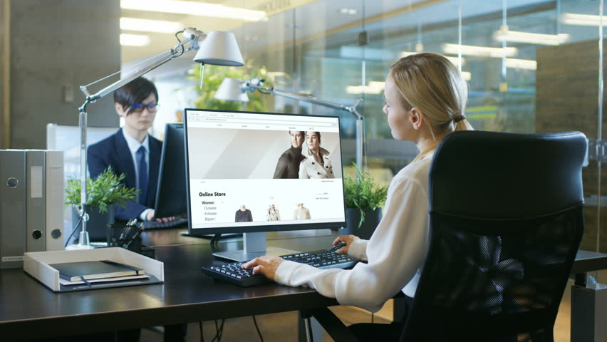 In the Office Businesswoman sits at Her Desk, Browsing Online Retail Clothing Web Page. Her Coworker Works at His Desk. Shot on RED EPIC-W 8K Helium Cinema Camera. | Shutterstock HD Video #1007506456