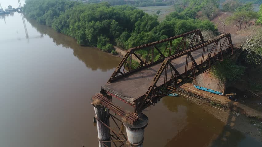 Flying around of supports old, rusty, dilapidated bridge over the river. Sun reflected in the water. Aerial view. | Shutterstock HD Video #1007523535