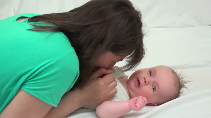 Mother playing with newborn baby lying on the bed | Shutterstock HD Video #1007525086