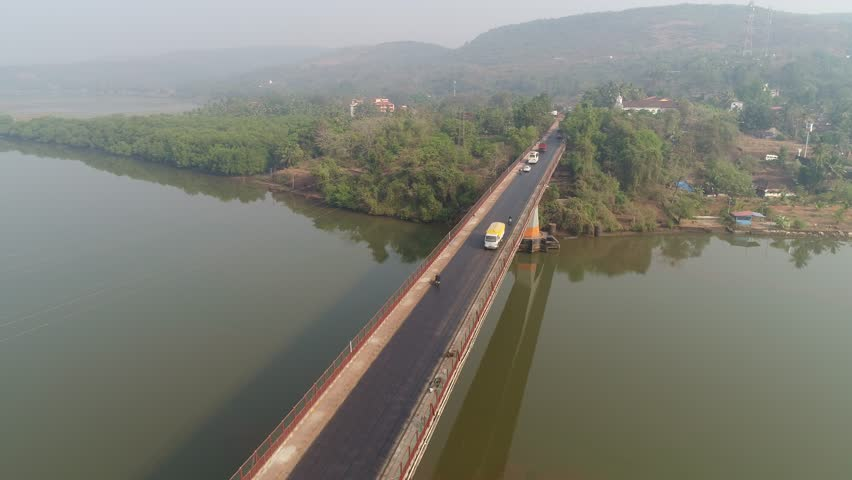 Flying over the bridge,cars goes on a large concrete bridge across the river. Aerial view. | Shutterstock HD Video #1007525977