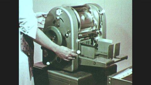 1950s: woman runs copies on mimeograph.