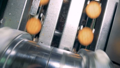 Top view of filling being put down on cookies by a factory machine
