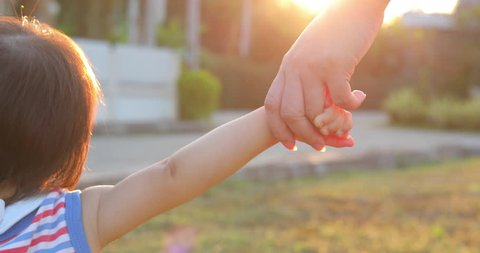 mother holding hand baby son walking together in lawn grass with beautiful light of sunset, feeling love family life concept scene