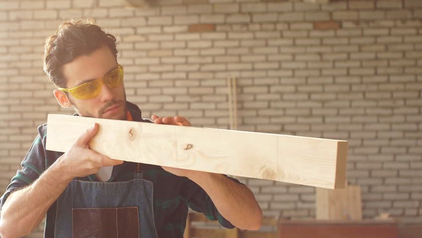 Carpenter checks the quality sanding wooden board. | Shutterstock HD Video #1007585746