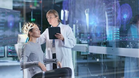 Woman Wearing Brainwave Scanning Headset Sits in a Chair while Scientist Adjusts the Device, Uses Tablet Computer. In the Modern Brain Study Laboratory Monitors Show EEG Reading and Brain Model. 4K.