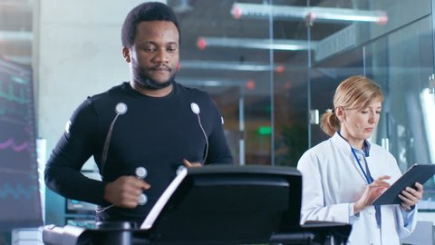 Male Athlete Runs on a Treadmill with Electrodes Attached to His Body while Sport Scientist Holds Tablet and Supervises EKG Status. In the Background Laboratory with High-Tech Equipment. 4K UHD.