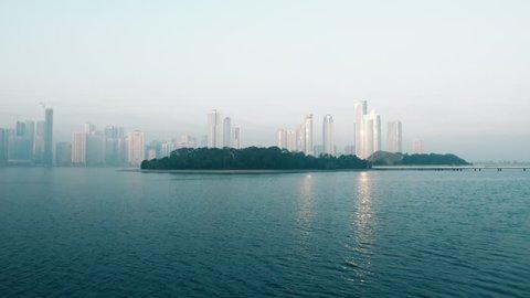 Panning along coast of Khalid lake. Skyline with skyscrapers. Al Noor island in Sharjah, UAE.