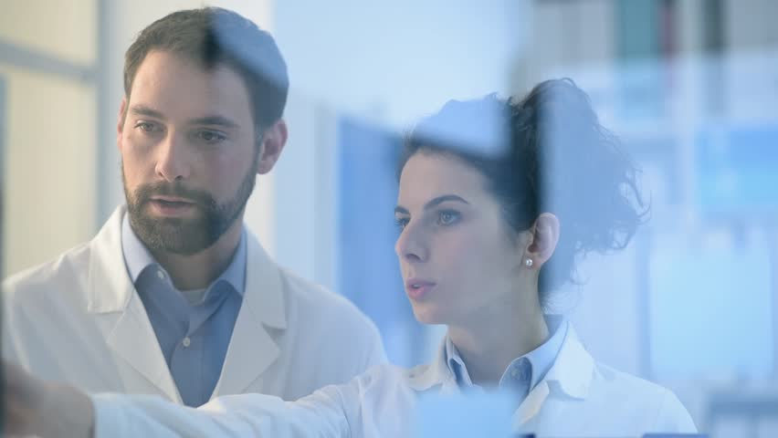 Doctors working together in the office, they are examining a patient's x-ray and discussing diagnosis and treatment, healthcare and medicine concept | Shutterstock HD Video #1007617216