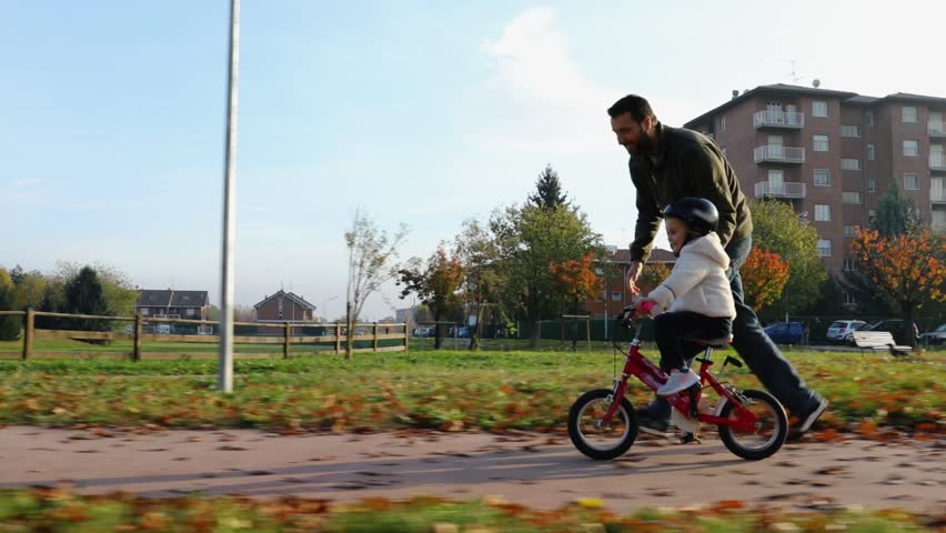 Father teaching daughter to ride bike at urban park. Child girl learning biking with the dad's help.Family and childhood concept.Sunny autumn day.Side gimbal follow 4k video  | Shutterstock HD Video #1007623246