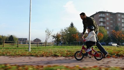 father teaching daughter to ride bike at urban park. Child girl learning biking with the dad's help.Family and childhood concept.Sunny autumn day.Side gimbal follow 4k video