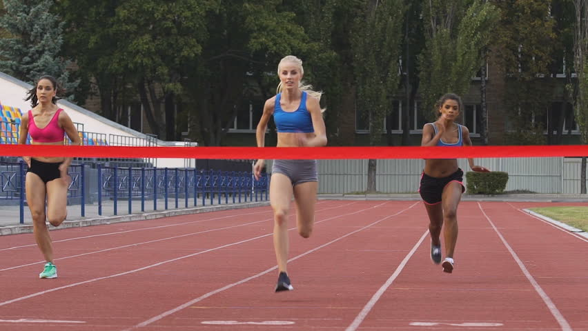 Female marathon runners crossing finishing line on professional sports arena. Fitness women racing competition at stadium, victory celebration, achievement. Motivated blond girl winning speed contest  #1007644546