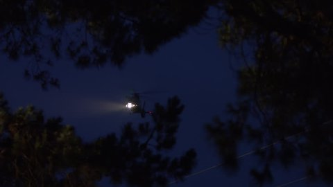 Helicopter flying in night operations with searchlight.