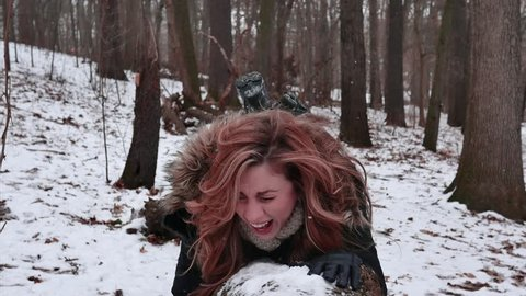 Woman almost falls of log lying in a winter wonderland