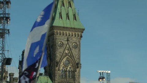 Waving quebec flag in front of parliament hill ottawa