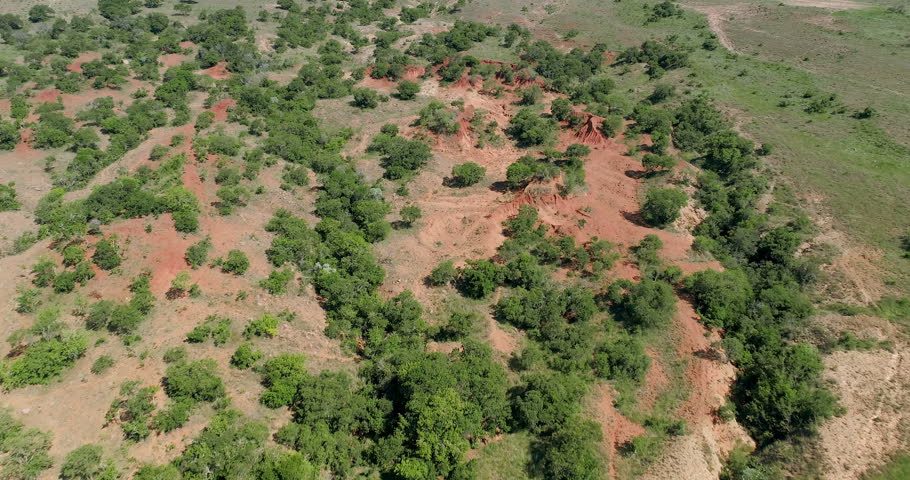 Gully erosion in red soil seen from the sky aerial 4K