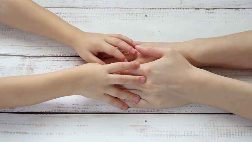 Hands of a child in the mother's hands close-up, hand in hand against the background of a wooden table, in slow motion. The child touches his mother's hands | Shutterstock HD Video #1007671066