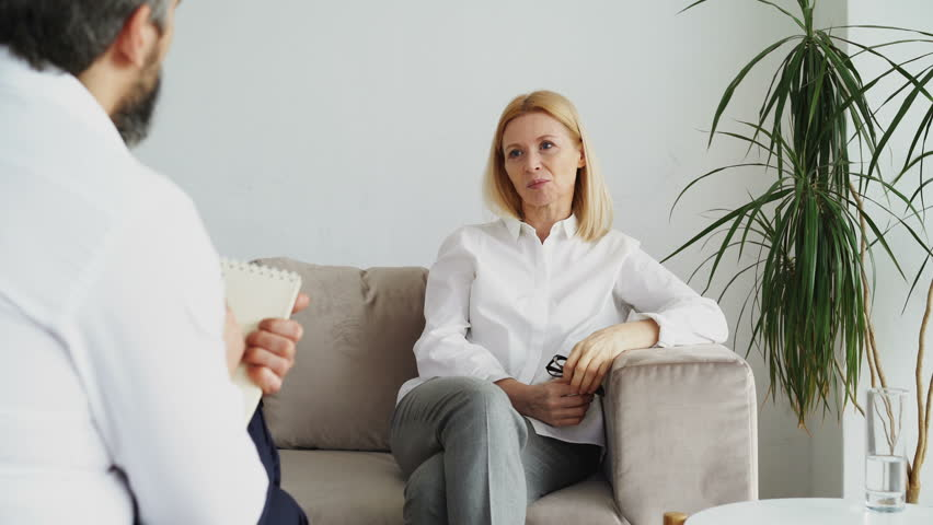 Male psychoanalyst listening adult female stressed patient and writing notes in psychologist office