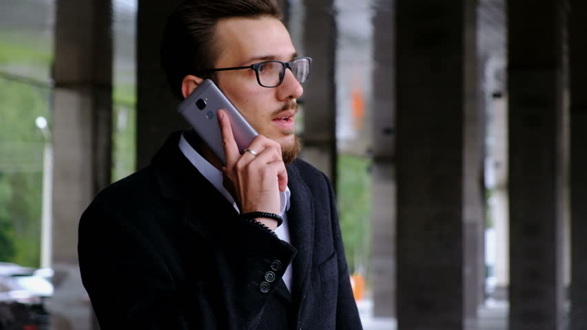 Portrait one serious manager in classic costume and in glasses stands on the street next to the office, answer to call and concentrated talk, holding the cell phone in his hand #1007691796