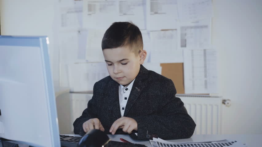 Little handsome boy hard working with computer and diagrams in office. 4K | Shutterstock HD Video #1007712361